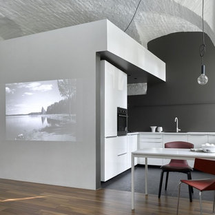 Inspiration for a contemporary l-shaped open plan kitchen in Moscow with a drop-in sink, flat-panel cabinets, white cabinets, black splashback, stainless steel appliances, slate floors, no island, black floor and white benchtop.