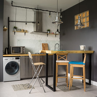 Foto på ett litet industriellt linjärt kök och matrum, med släta luckor, skåp i rostfritt stål, träbänkskiva och glaspanel som stänkskydd