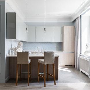 Стильный дизайн: п-образная кухня в стиле современная классика с плоскими фасадами, белой столешницей, светлыми деревянными фасадами, синим фартуком, фартуком из плитки кабанчик, техникой под мебельный фасад, полуостровом, серым полом, полом из керамогранита и столешницей из акрилового камня - последний тренд