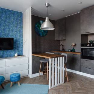 На фото: параллельная кухня-гостиная в современном стиле с плоскими фасадами, серыми фасадами, деревянной столешницей, серым фартуком, черной техникой, паркетным полом среднего тона, полуостровом, коричневым полом и коричневой столешницей с