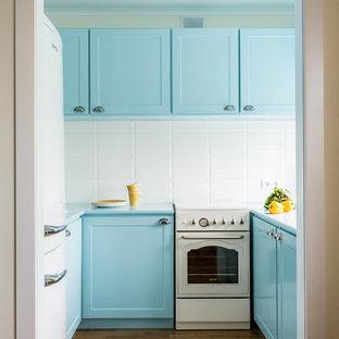 Aménagement d'une petite cuisine rétro en L fermée avec des portes de placard turquoises, sol en stratifié, un sol marron et un plan de travail turquoise.
