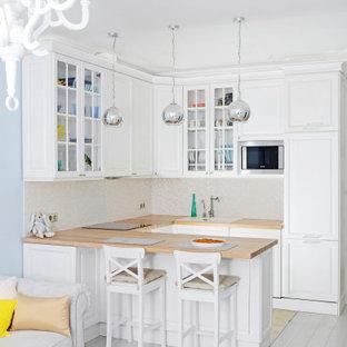 Immagine di una cucina classica con lavello da incasso, ante con bugna sagomata, ante bianche, top in legno, paraspruzzi bianco, elettrodomestici in acciaio inossidabile, pavimento in legno verniciato, penisola, pavimento bianco e top marrone