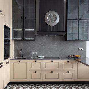 Идея дизайна: кухня среднего размера в стиле современная классика с врезной раковиной, фасадами с выступающей филенкой, бежевыми фасадами, столешницей из кварцевого агломерата, серым фартуком, фартуком из каменной плиты, черной техникой, полом из керамической плитки, серой столешницей, полуостровом и разноцветным полом