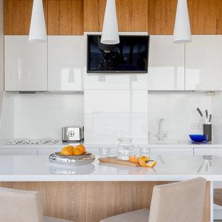 Источник вдохновения для домашнего уюта: кухня в современном стиле с плоскими фасадами, белыми фасадами, белым фартуком, островом и белой столешницей