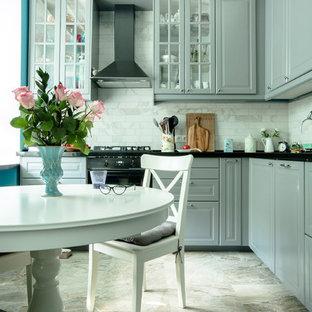 Пример оригинального дизайна: угловая кухня в стиле современная классика с серыми фасадами, серым фартуком, черной техникой и бежевым полом
