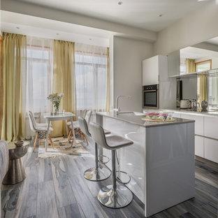 Неиссякаемый источник вдохновения для домашнего уюта: кухня-гостиная в скандинавском стиле с плоскими фасадами, белыми фасадами, островом, врезной раковиной, фартуком из зеркальной плитки, коричневым полом и серой столешницей