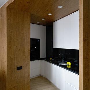 Свежая идея для дизайна: маленькая угловая кухня-гостиная в современном стиле с монолитной раковиной, плоскими фасадами, белыми фасадами, столешницей из акрилового камня, черным фартуком, черной столешницей, черной техникой и бежевым полом без острова - отличное фото интерьера