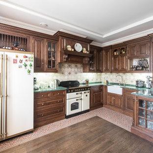 На фото: п-образная кухня-гостиная в викторианском стиле с раковиной в стиле кантри, фасадами с выступающей филенкой, темными деревянными фасадами, серым фартуком и белой техникой без острова