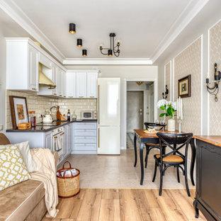 Идея дизайна: угловая кухня-гостиная среднего размера в классическом стиле с фасадами с выступающей филенкой, белыми фасадами, бежевым фартуком, фартуком из плитки кабанчик, бежевым полом и черной столешницей