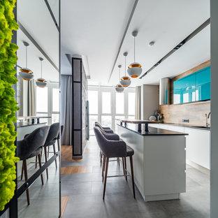 Идея дизайна: кухня в современном стиле с плоскими фасадами, белыми фасадами, коричневым фартуком, островом, серым полом и серой столешницей