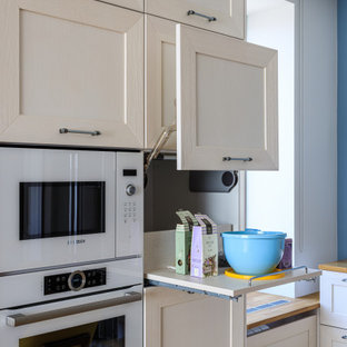 Inspiration for a large scandinavian galley eat-in kitchen in Moscow with a drop-in sink, recessed-panel cabinets, white cabinets, wood benchtops, blue splashback, white appliances, medium hardwood floors, no island, brown floor and beige benchtop.