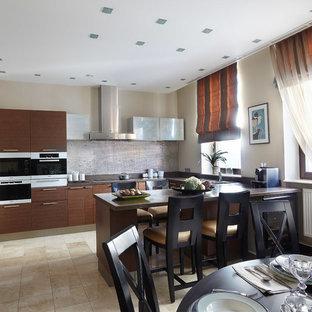 На фото: п-образная кухня в современном стиле с обеденным столом, плоскими фасадами, темными деревянными фасадами и белой техникой с