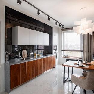 Идея дизайна: линейная кухня в современном стиле с обеденным столом, плоскими фасадами, фасадами цвета дерева среднего тона, черным фартуком, белым полом, серой столешницей, одинарной раковиной и фартуком из каменной плиты без острова