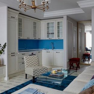 На фото: угловые кухни-гостиные в стиле современная классика с фасадами с выступающей филенкой, белыми фасадами, синим фартуком, фартуком из стекла, белой техникой, белым полом и белой столешницей без острова