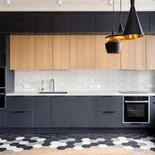 Идея дизайна: линейная кухня среднего размера в скандинавском стиле с обеденным столом, врезной раковиной, плоскими фасадами, черными фасадами, столешницей из акрилового камня, белым фартуком, фартуком из керамической плитки, черной техникой, полом из керамической плитки, белой столешницей и разноцветным полом без острова