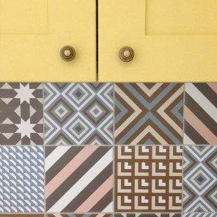 Bild på ett mellanstort funkis brun brunt kök, med en undermonterad diskho, luckor med upphöjd panel, gula skåp, laminatbänkskiva, rosa stänkskydd, stänkskydd i keramik, rostfria vitvaror, klinkergolv i keramik och beiget golv