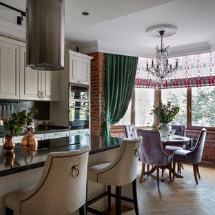 Идея дизайна: прямая кухня в классическом стиле с обеденным столом, накладной раковиной, белыми фасадами, черным фартуком, островом и бежевым полом