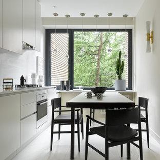 На фото: прямая кухня в современном стиле с обеденным столом, плоскими фасадами, белым полом, белой столешницей и черно-белыми фасадами без острова