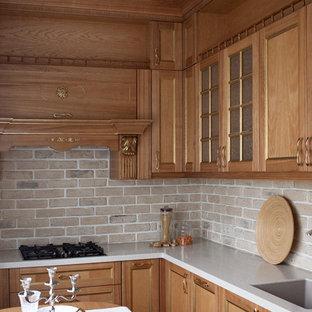На фото: маленькая отдельная, угловая кухня в стиле неоклассика (современная классика) с фасадами с утопленной филенкой, столешницей из акрилового камня, бежевым фартуком, фартуком из кирпича, врезной раковиной, светлыми деревянными фасадами и белой столешницей без острова с