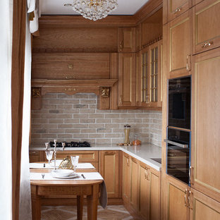 Design ideas for a small transitional l-shaped separate kitchen in Moscow with recessed-panel cabinets, solid surface benchtops, beige splashback, brick splashback, black appliances, porcelain floors, no island, an undermount sink, light wood cabinets, beige floor and white benchtop.