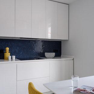 Новый формат декора квартиры: кухня в современном стиле с белыми фасадами, синим фартуком, фартуком из плитки мозаики и белой столешницей без острова