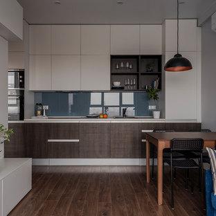 Новый формат декора квартиры: линейная кухня-гостиная в современном стиле с накладной раковиной, плоскими фасадами, синим фартуком, фартуком из стекла, черной техникой, темным паркетным полом, коричневым полом, белой столешницей и темными деревянными фасадами без острова