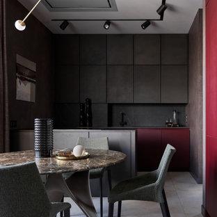 Стильный дизайн: параллельная кухня среднего размера в современном стиле с обеденным столом, плоскими фасадами, черными фасадами, черным фартуком, черной техникой, полом из керамогранита, полуостровом, серым полом и черной столешницей - последний тренд