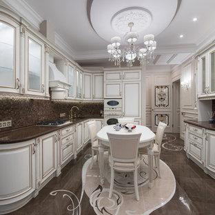 Свежая идея для дизайна: п-образная кухня среднего размера в классическом стиле с обеденным столом, врезной раковиной, фасадами с выступающей филенкой, белыми фасадами, коричневым фартуком, фартуком из плитки мозаики, техникой под мебельный фасад, коричневым полом и коричневой столешницей - отличное фото интерьера