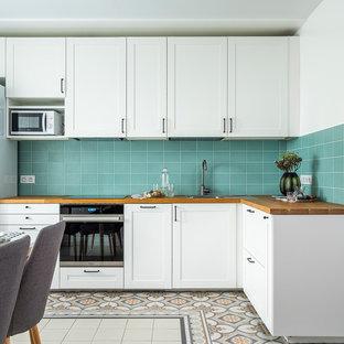 Идея дизайна: угловая кухня в современном стиле с фасадами в стиле шейкер, белыми фасадами, столешницей из дерева, коричневой столешницей, обеденным столом, накладной раковиной, синим фартуком, белой техникой и разноцветным полом без острова