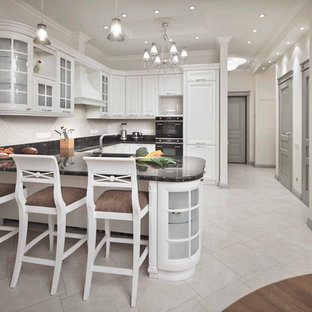 Photo of a mid-sized transitional u-shaped eat-in kitchen in Moscow with an undermount sink, raised-panel cabinets, white cabinets, marble benchtops, beige splashback, porcelain splashback, black appliances, porcelain floors, beige floor, black benchtop and a peninsula.