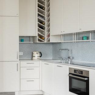 На фото: угловые кухни в современном стиле с врезной раковиной, фасадами с декоративным кантом, белыми фасадами, серым фартуком, техникой из нержавеющей стали, серым полом и белой столешницей