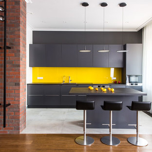 Пример оригинального дизайна: прямая кухня-гостиная в современном стиле с плоскими фасадами, черными фасадами, желтым фартуком, фартуком из стекла, островом, белым полом, черной столешницей и техникой из нержавеющей стали