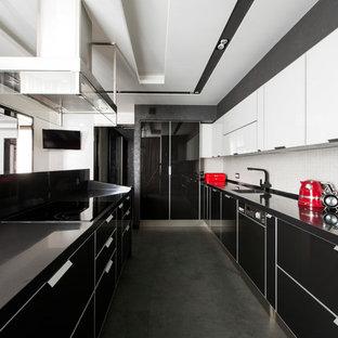 На фото: п-образная кухня в современном стиле с врезной раковиной, плоскими фасадами, белым фартуком, островом, черным полом и черной столешницей с