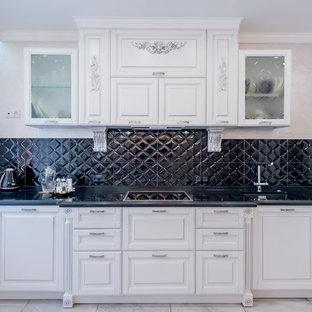 На фото: угловая кухня-гостиная в классическом стиле с врезной раковиной, фасадами с выступающей филенкой, белыми фасадами, черным фартуком, техникой из нержавеющей стали, бежевым полом и черной столешницей с