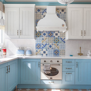 Mid-sized mediterranean u-shaped separate kitchen in Moscow with solid surface benchtops, multi-coloured splashback, ceramic splashback, white appliances, ceramic floors, no island, multi-coloured floor, white benchtop, recessed-panel cabinets, blue cabinets and an integrated sink.