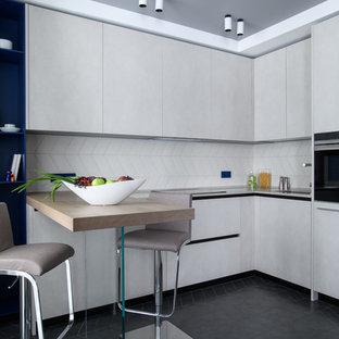 Пример оригинального дизайна: отдельная, угловая кухня в современном стиле с серыми фасадами, белым фартуком, черной техникой, черным полом и черной столешницей
