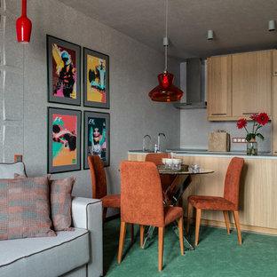 На фото: параллельная кухня-гостиная в современном стиле с накладной раковиной, плоскими фасадами, светлыми деревянными фасадами, серым фартуком, островом, зеленым полом, ковровым покрытием, техникой под мебельный фасад и серой столешницей с