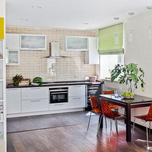 На фото: угловые кухни-гостиные в современном стиле с плоскими фасадами, белыми фасадами, бежевым фартуком, техникой из нержавеющей стали и коричневым полом без острова