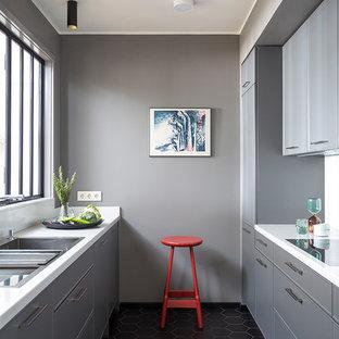 Новый формат декора квартиры: параллельная кухня среднего размера в современном стиле с столешницей из кварцевого композита, полом из керамогранита, накладной раковиной, серыми фасадами и черным полом без острова