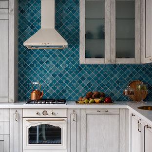 モスクワの中くらいのトランジショナルスタイルのおしゃれなキッチン (レイズドパネル扉のキャビネット、淡色木目調キャビネット、人工大理石カウンター、青いキッチンパネル、セラミックタイルのキッチンパネル、白い調理設備、セラミックタイルの床、アイランドなし、ターコイズの床、ドロップインシンク) の写真