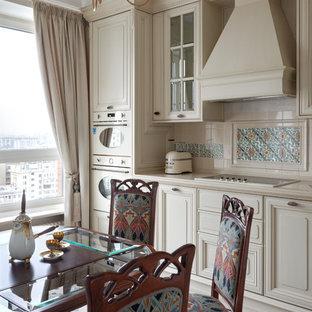 Diseño de cocina clásica, sin isla, con armarios con paneles con relieve, puertas de armario beige, salpicadero beige, electrodomésticos blancos, suelo de baldosas de cerámica y suelo multicolor