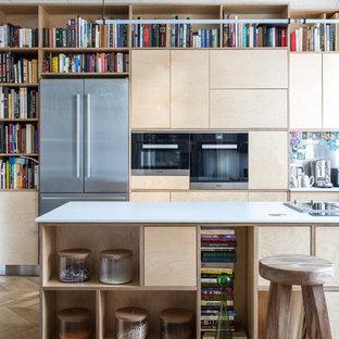 На фото: кухня в стиле современная классика с обеденным столом, плоскими фасадами, бежевыми фасадами, техникой из нержавеющей стали, паркетным полом среднего тона, островом, бежевым полом и белой столешницей с