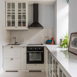 This is an example of a small classic single-wall enclosed kitchen in Moscow with a built-in sink, raised-panel cabinets, white cabinets, beige splashback, metro tiled splashback, black appliances and no island.