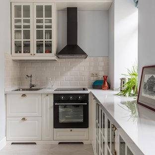 Пример оригинального дизайна: маленькая отдельная, линейная кухня в стиле современная классика с накладной раковиной, фасадами с выступающей филенкой, белыми фасадами, бежевым фартуком, фартуком из плитки кабанчик и черной техникой без острова
