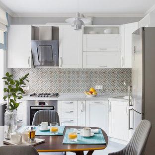Удачное сочетание для дизайна помещения: угловая кухня-гостиная в современном стиле с врезной раковиной, фасадами в стиле шейкер, белыми фасадами, техникой из нержавеющей стали, разноцветным фартуком и серым полом без острова - самое интересное для вас
