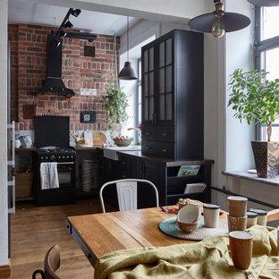 Идея дизайна: угловая кухня в стиле лофт с обеденным столом, раковиной в стиле кантри, фасадами в стиле шейкер, черными фасадами, деревянной столешницей, черной техникой, паркетным полом среднего тона, коричневым полом и коричневой столешницей без острова