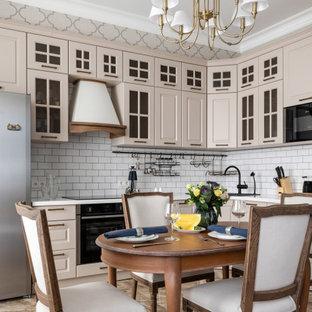 Идея дизайна: угловая кухня в классическом стиле с стеклянными фасадами, бежевыми фасадами, белым фартуком, фартуком из плитки кабанчик, черной техникой, бежевым полом и белой столешницей