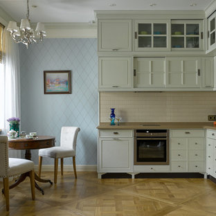 This is an example of a traditional l-shaped open plan kitchen in Moscow with recessed-panel cabinets, beige splashback, stainless steel appliances, medium hardwood floors, no island, an undermount sink and white cabinets.
