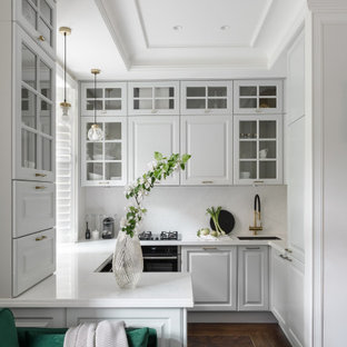 Пример оригинального дизайна: п-образная кухня-гостиная среднего размера в скандинавском стиле с врезной раковиной, серыми фасадами, столешницей из кварцевого агломерата, белым фартуком, фартуком из кварцевого агломерата, черной техникой, полом из винила, полуостровом, коричневым полом, белой столешницей и фасадами с выступающей филенкой
