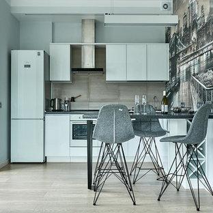 Стильный дизайн: кухня-гостиная в современном стиле с плоскими фасадами, белыми фасадами, серым фартуком, белой техникой, светлым паркетным полом, полуостровом и серой столешницей - последний тренд